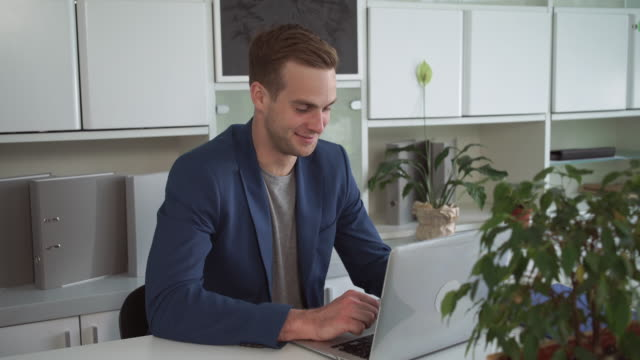 Happy-businessman-working-on-the-laptop-in-the-modern-office