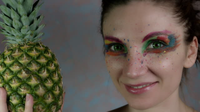 4k-Shot-of-a-Woman-with-Multicoloured-Make-up-Biting-Pineapple