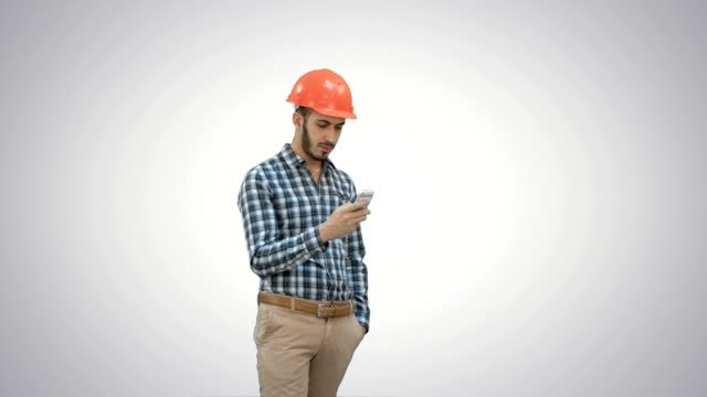 Young-manager-in-helmet-using-mobile-phone-on-white-background