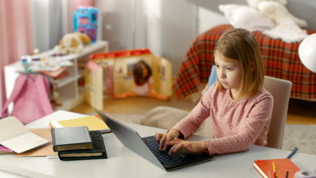 Long-Shot-of-a-Cute-Young-Girls-Typing-on-Laptop-while-Sitting-at-Table-in-Her-Room-