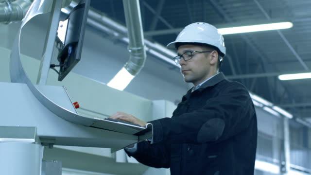 Ingeniero-en-casco-montando-en-CNC-la-máquina-en-la-fábrica
