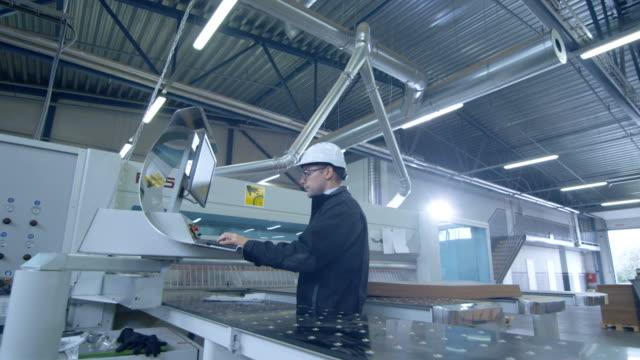 Ingeniero-en-Hard-Hat-configuración-de-máquina-CNC-en-la-fábrica