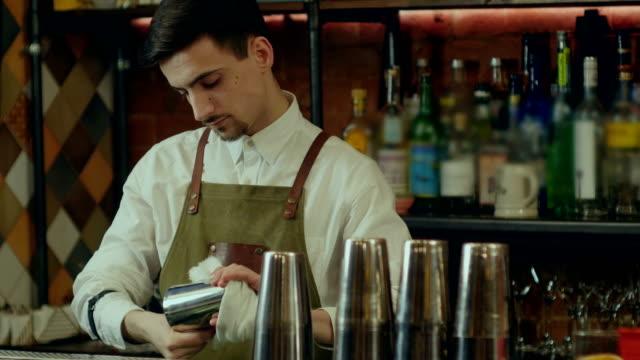 Barman-rub-metal-shakes-with-napkin-at-work-place