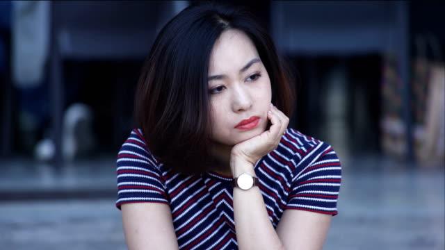 Mujer-asiática-solitaria-pensativa-sentado-en-la-ciudad:-Closeup-Retrato-mujer-triste
