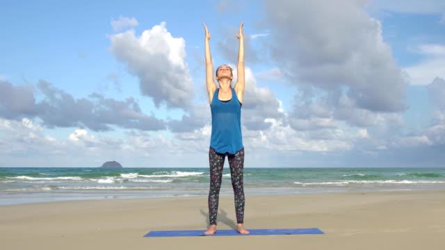 Mujer-joven-balance-ejercicio-de-yoga-en-la-playa-frente-a-mar-Concepto-de-estilo-de-vida-activa-saludable-