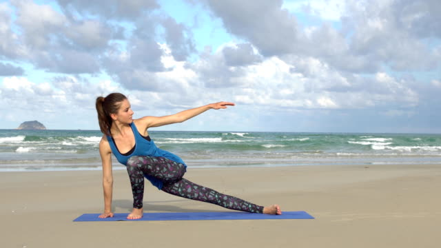 Woman-practicing-yoga-on-the-beach-at-sunset-