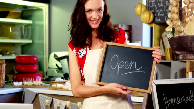 Portrait-of-a-female-staff-holding-a-open-sign
