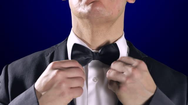 Hombre-fijación-pajarita-cerca-smoking-traje-fondo-azul-oscuro