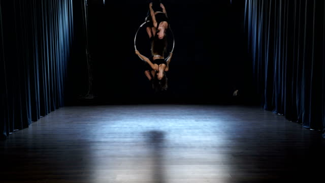 Flexible-girls-makes-a-gymnastic-elements-on-the-aerial-hoop