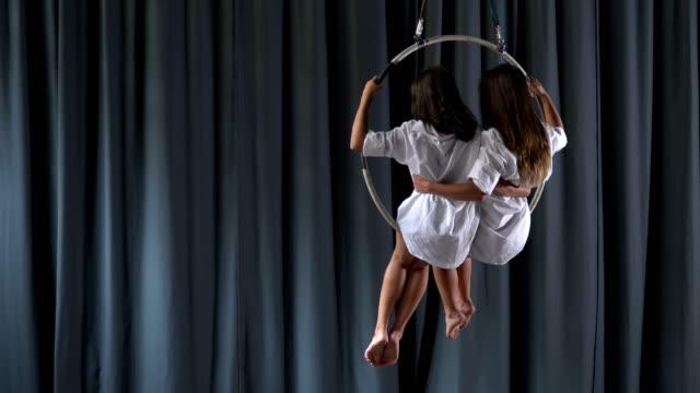 Two-girls-sways-in-the-aerial-hoop