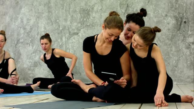 Retrato-de-sonriente-ajuste-usando-la-tableta-digital-mientras-estaba-sentado-en-la-estera-de-yoga-después-de-entrenamiento-de-fitness-de-mujeres