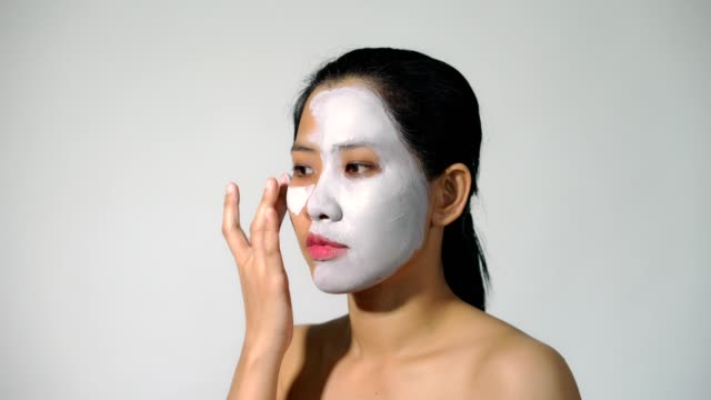 Junge-Frau-Ton-Gesicht-Maske-Peeling-natürlich-mit-reinigende-Maske-auf-ihr-Gesicht-auf-weißem-Hintergrund