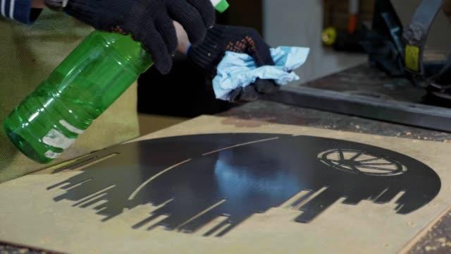 Blacksmith-preparing-decorative-metal-detail-for-paint-at-his-workshop