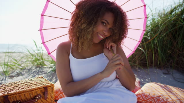 Portrait-of-African-American-female-picnicking-on-beach