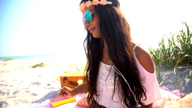 Indian-American-female-listening-music-at-beach-picnic
