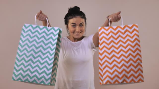 cheerful-female-shows-shopping-bag