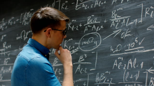 Académico-joven-brillante-acabados-escritura-grande-y-compleja-fórmula-matemática-/-ecuación-en-la-pizarra-