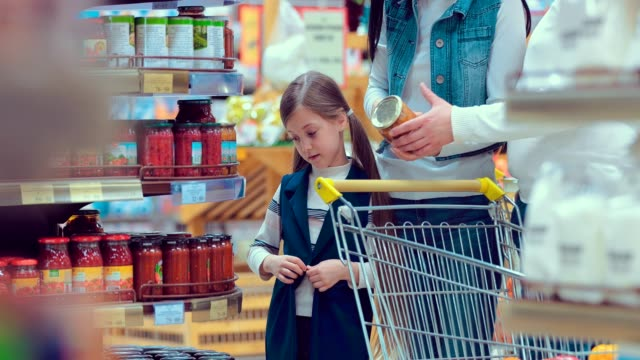 Portrait-of-a-little-girl-who-chooses-cans-in-a-supermarket-with-her-family