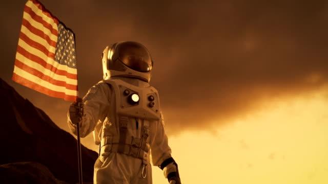 Astronauta-con-traje-espacial-planta-la-bandera-estadounidense-en-el-planeta-rojo-/-Marte-Momento-patriótico-y-orgullo-para-toda-la-humanidad-Recorrido-de-espacio-y-concepto-de-colonización-