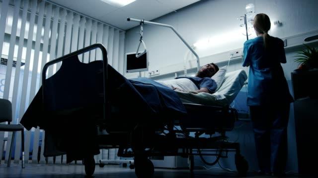Bajo-nivel-rodado-en-el-Hospital-muy-enfermo-acostado-en-la-cama-contra-enfermera-comprueba-sus-signos-vitales-y-la-gota-