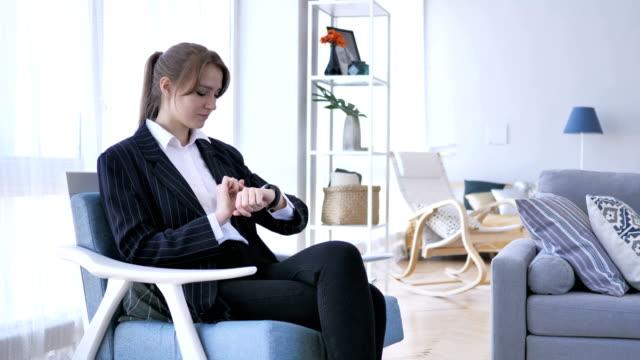 Frau-mit-Hilfe-Smartwatch-sitzend-auf-Sofa