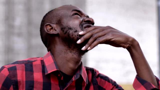 Hombre-negro-preocupado-y-pensativo-mirando-para-arriba-al-aire-libre