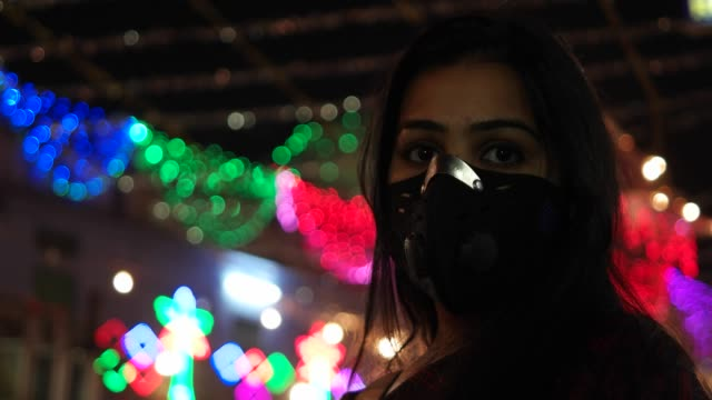 Young-Indian-woman-wears-pollution-mask-to-protect-from-pollutants-breath-lungs-health-emergency-precaution-safety-measure-face-cover-in-a-crowded-busy-Indian-town-danger-protect-handheld-particulate