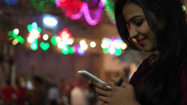 Young-Indian-woman-on-a-touch-screen-smart-mobile-phone-texts-messages-types-shares-photo-video-calls-in-front-of-a-festival-colorful-bright-lights-out-of-focus-in-the-background-celebration-mela-love