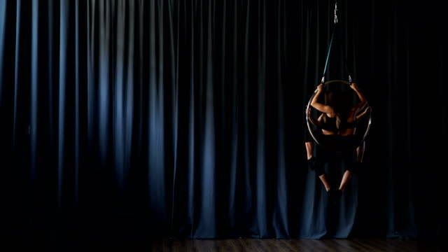 Charming-gymnasts-performs-a-trick-in-the-aerial-hoop