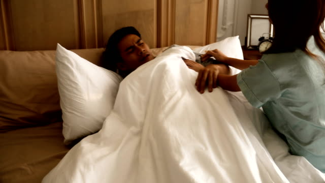 Young-wife-woke-her-husband-to-wake-up-on-the-bed