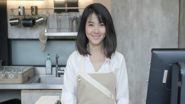 Porträt-von-asiatischen-weiblichen-Barista-über-Hände-und-lächelnd-auf-die-Kamera-im-Kaffee-café