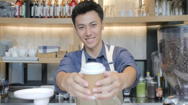 Kaffee-Business-Konzept---schöne-kaukasischen-Dame-lächelt-in-die-Kamera-bietet-Einweg-Take-away-heißen-Kaffee-im-modernen-Café