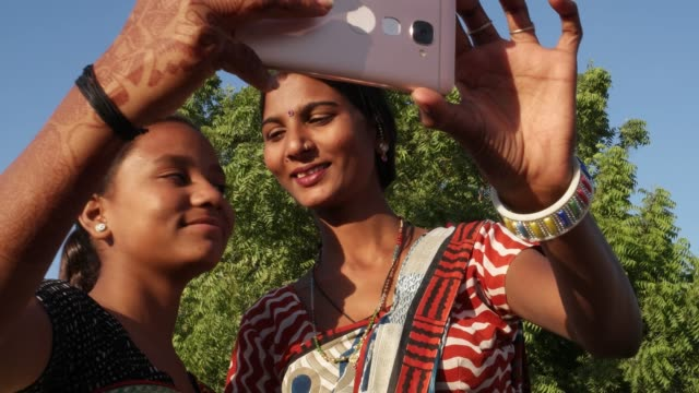 Two-ladies-laughing-smiling-taking-selfie-video-photo-together-with-a-smart-phone-helping-each-other-bonding-love-handheld-assist-medium-shot-in-traditional-Rajasthani-costume-in-sunny-outdoor-setting