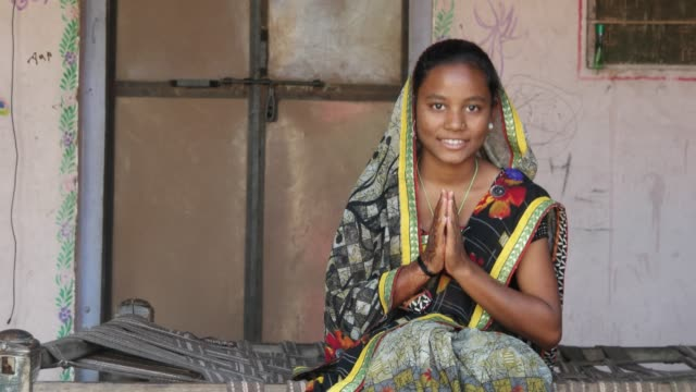 Mid-shot-of-Indian-teenager-girl-sitting-at-home-with-sari-dress-traditional-namaste-respect-covered-head-looking-at-camera-joining-henna-tattooed-hands-for-greeting-smiling-content-adjust-static