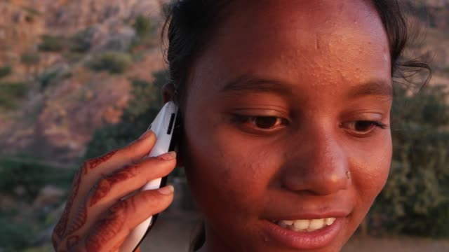 Teenage-girl-dials-talks-idea-smart-mobile-phone-looking-around-outdoor-nature-hill-top-smile-happy-joy-fun-panoramic-view-viewpoint-sunset-dusk-on-a-hot-summer-day-in-India-handheld-stabilized-sand