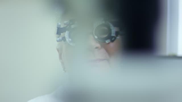 Senior-mujer-posando-en-el-marco-de-prueba-en-clínica-de-atención-oftalmológica