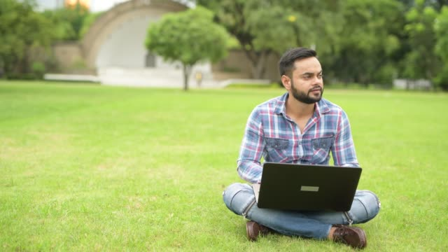Young-Handsome-Indian-Man-In-Park-Using-Laptop-Computer