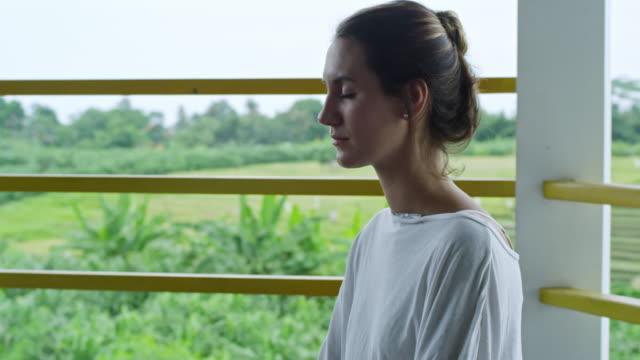 Mujer-caucásica-de-práctica-de-la-meditación-en-el-balcón