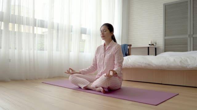 mujer-haciendo-meditación-sobre-el-suelo-de-madera