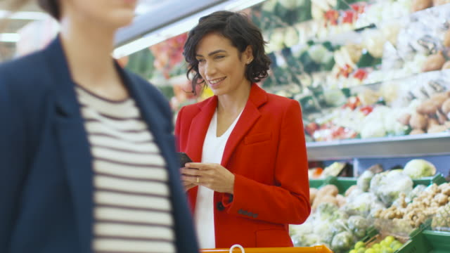 At-the-Supermarket:-Beautiful-Woman-Uses-Smartphone-while-Standing-in-the-Fresh-Produce-Section-of-the-Store-Woman-Immersed-in-Internet-Surfing-on-Her-Mobile-Phone-In-the-Background-Colorful-Fruits-and-Organic-Vegetables-
