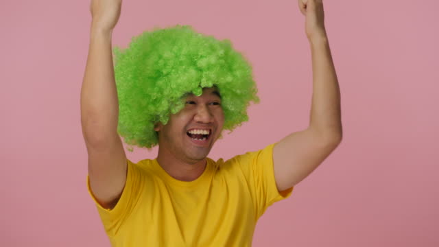 Young-crazy-man-with-colored-afro-wig-expressing-happiness-on-pink-background-