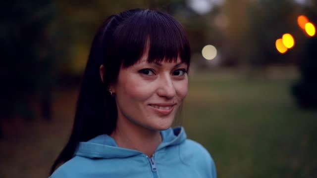 Primer-plano-retrato-de-hermosa-morena-con-cola-de-caballo-usar-brillante-con-capucha-mirando-a-cámara-y-sonriendo-de-pie-en-el-parque-por-la-tarde-en-otoño-