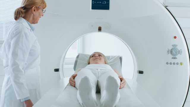 In-the-Medical-Laboratory-Female-Patient-Lying-on-a-CT-or-MRI-Scan-Bed-Undergoes-Scanning-Procedure-Under-Supervision-of-Professional-Radiologist-Front-View-Camera-Shot-
