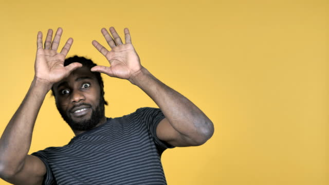 Casual-African-Man-Confused-and-Scared-of-Problems-Isolated-on-Yellow-Background