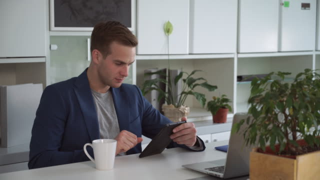 Businessman-about-30s-reading-on-the-touch-screen-tablet