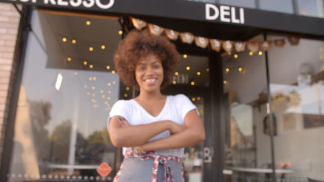 Black-female-owner-walks-into-focal-plane-in-front-of-cafe