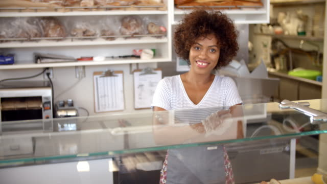 Female-business-owner-behind-the-counter-at-a-sandwich-bar