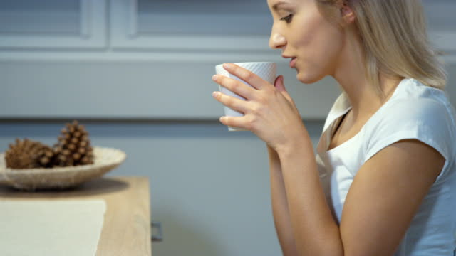 Cheerful-young-woman-holding-mug-in-the-kitchen-at-home-