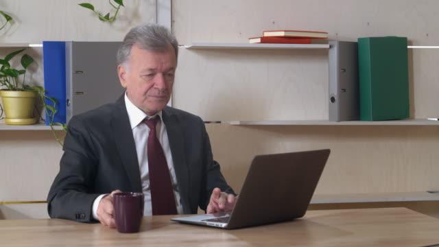 anciano-director-usar-Laptop-en-el-trabajo