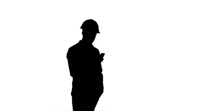 Silhouette-Young-manager-in-helmet-using-mobile-phone